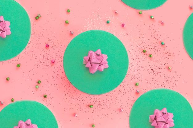 Scatola regalo verde biscotto rotonda con motivo a composizione aperta in nastro rosa con jingle bells e glitter su sfondo rosa Foto Premium
