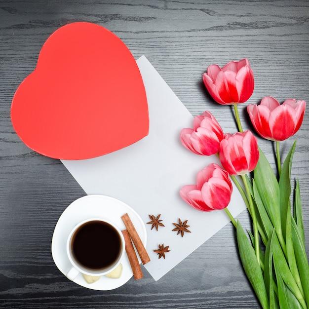 Scatola rossa a forma di cuore, tulipani rosa, lenzuolo grigio e una tazza di caffè Foto Premium