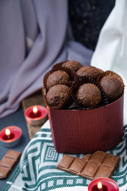 Scatola rossa di cioccolatini, barretta di latte e candele fiammeggianti sulla tovaglia Foto Gratuite