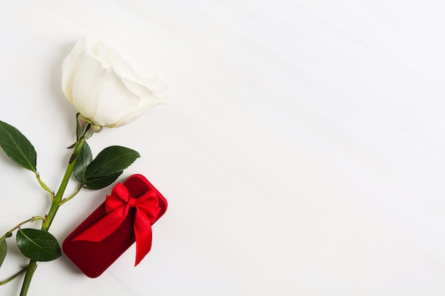 Scatola rossa per gioielli con l'arco rosso e la rosa bianca su fondo strutturato bianco. san valentino o concetto di matrimonio. segno d'amore. copia spazio Foto Premium
