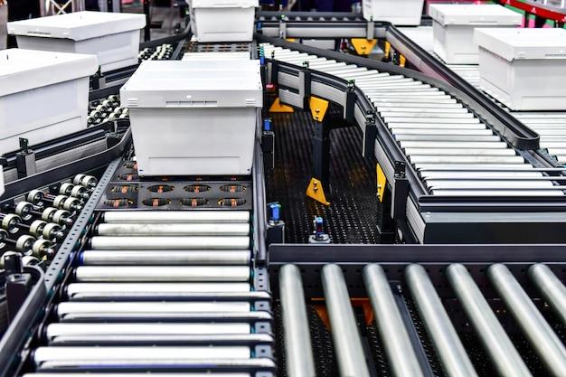 Scatole di cartone bianche sul nastro trasportatore concetto di sistema di trasporto pacchi Foto Premium