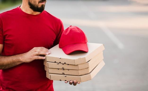 Scatole per pizza della tenuta del tipo di consegna del primo piano Foto Gratuite