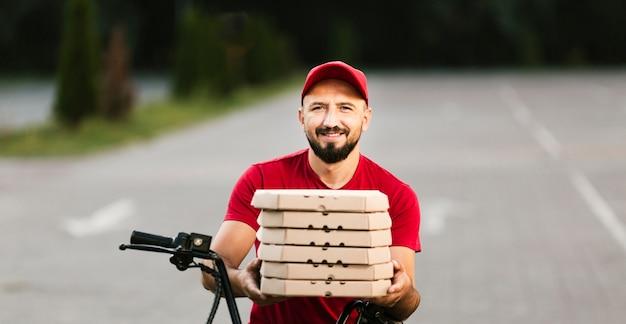 Scatole per pizza della tenuta del tipo di consegna di smiley di vista frontale Foto Gratuite