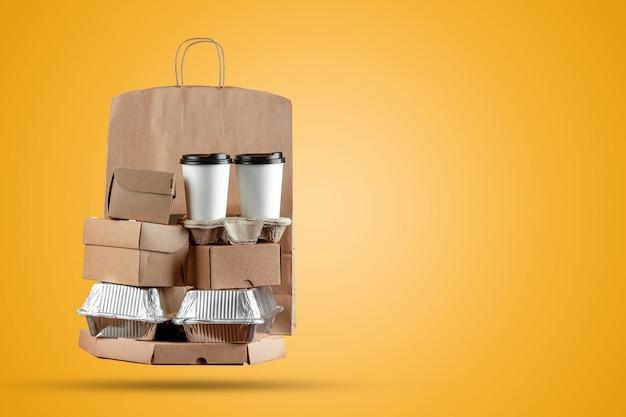 Scatole per pizza e cibo consegna sacchetto di carta con una tazza di caffè usa e getta e una scatola di wok su uno sfondo giallo Foto Premium