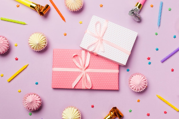Scatole regalo avvolte circondate da candele; corno di festa; spruzzatori; scatole da regalo; aalaw su sfondo rosa Foto Gratuite