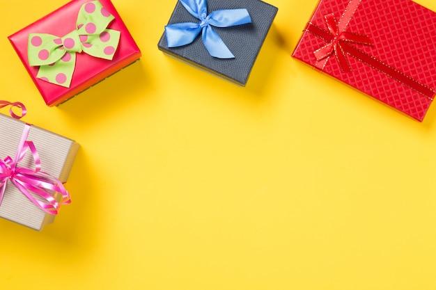 Scatole regalo colorate su sfondo giallo Foto Premium