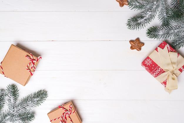 Scatole regalo con rami di abete di neve e biscotti stelle su un fondo di legno bianco. biglietto natalizio. copriletto piatto Foto Premium