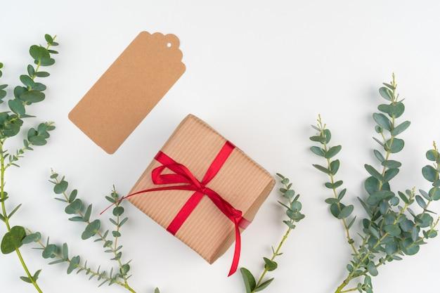 Scatole regalo confezionate in carta artigianale con decorazioni semplici di rami di piante verdi Foto Premium