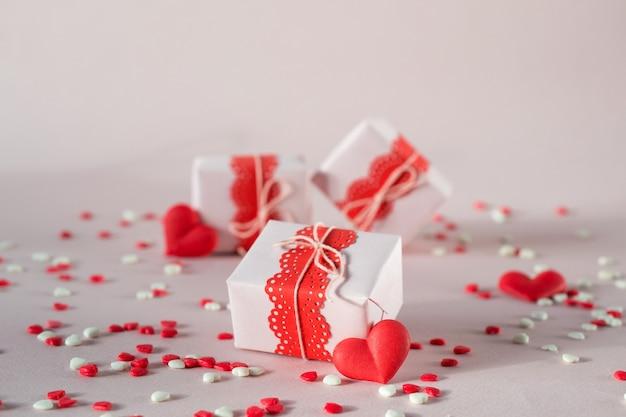 Scatole regalo di san valentino con regali e decorazioni. su sfondo rosa con granelli. Foto Premium