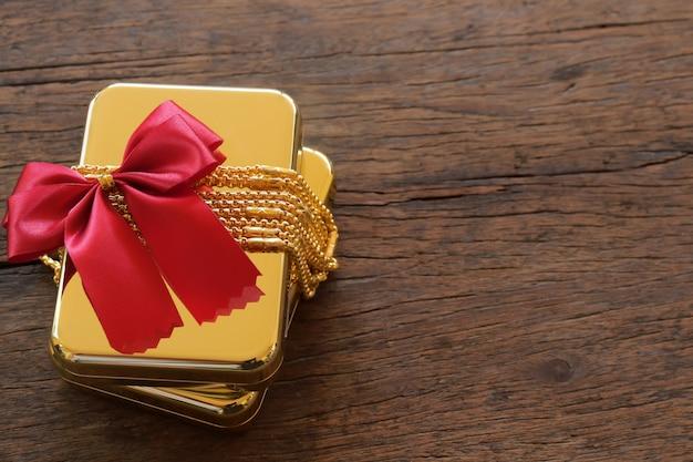 Scatole regalo in oro con collana in oro e nastro su fondo di legno marrone Foto Premium