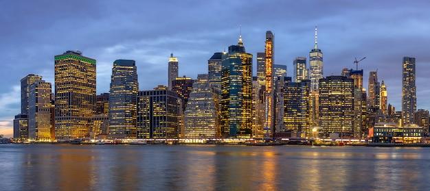 Scena di panorama di new york cityscape con il ponte di brooklyn accanto al fiume est al tempo crepuscolare Foto Premium