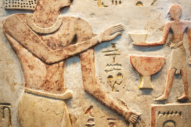 Scena egitto antico. sculture in geroglifico colorate sul muro. murales antico egitto. Foto Premium
