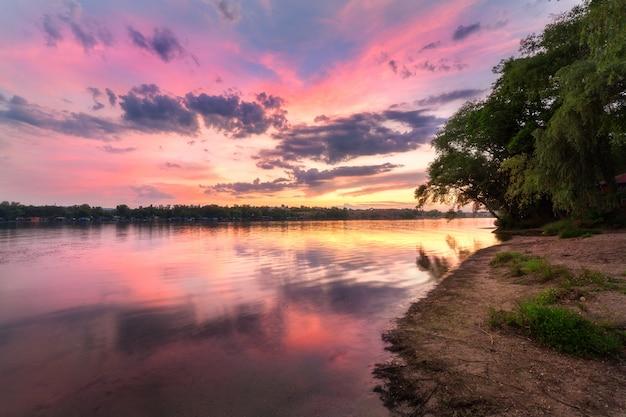 Scena tranquilla con fiume e cielo colorato con nuvole al tramonto Foto Premium