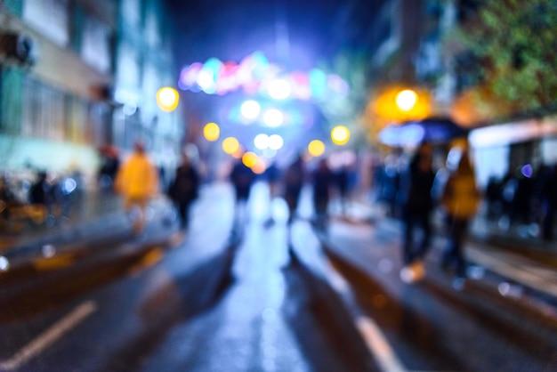 Scena urbana di notte con la gente che cammina sfuocato con fondo colorato. Foto Premium