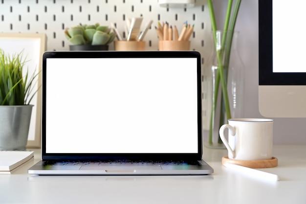 Scenario della scrivania con il computer portatile dello schermo in bianco del modello. area di lavoro minima Foto Premium