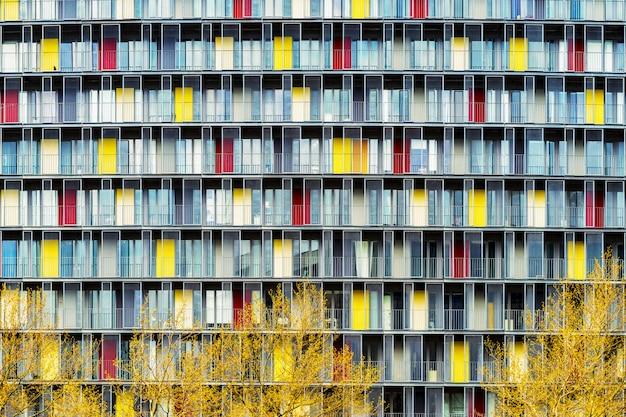 Scenario mozzafiato di un edificio con porte colorate nel mezzo di una città durante l'autunno Foto Gratuite