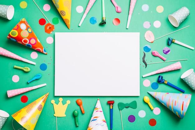 Scheda bianca vuota decorata con oggetti di compleanno e coriandoli su sfondo verde Foto Gratuite