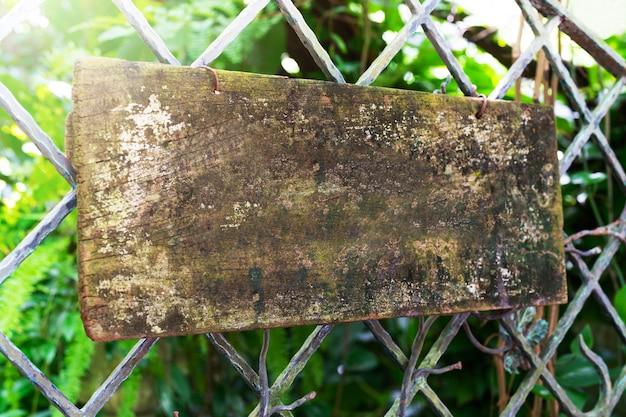 Scheda di legno che appende sulla rete fissa d'acciaio Foto Premium