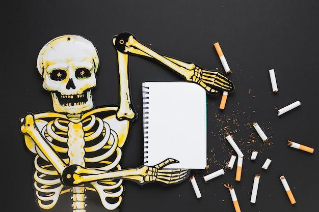 Scheletro di vista superiore con sigarette e notebook Foto Gratuite