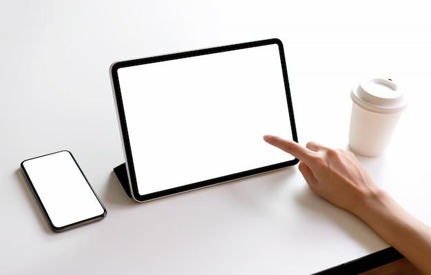 Schermo del tablet e dello smartphone vuoto sul mockup del tavolo per promuovere i tuoi prodotti. Foto Premium