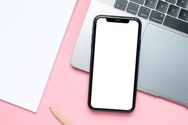 Schermo in bianco del telefono cellulare, computer portatile e taccuino di affari sul rosa con lo spazio della copia Foto Premium