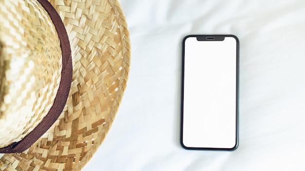 Schermo vuoto di vista superiore dello smartphone su stanza e cappello, durante il tempo libero. Foto Premium