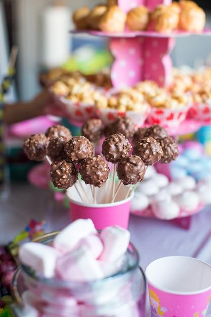 Schiocchi e popcorn della torta di cioccolato sulla tavola del dessert alla festa di compleanno del bambino Foto Premium