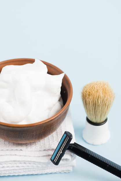 Schiuma in ciotola di legno sul tovagliolo piegato bianco con la spazzola ed il rasoio di rasatura contro fondo blu Foto Gratuite