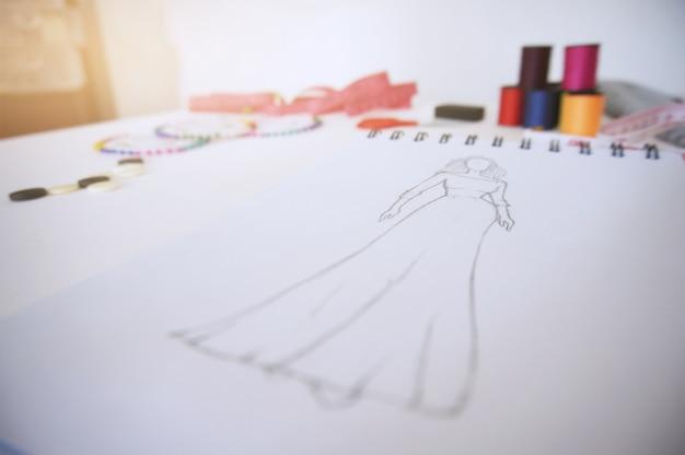 Schizzi di abbigliamento di moda design disegno in atelier. concetto di design creativo Foto Premium
