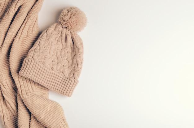 Sciarpa lavorata a maglia una pipa o un colletto dai fili caldi e un berretto beige con un pompon. Foto Premium