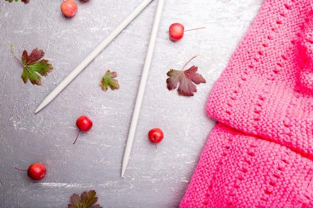 Sciarpa rosa vicino ai ferri da maglia Foto Premium