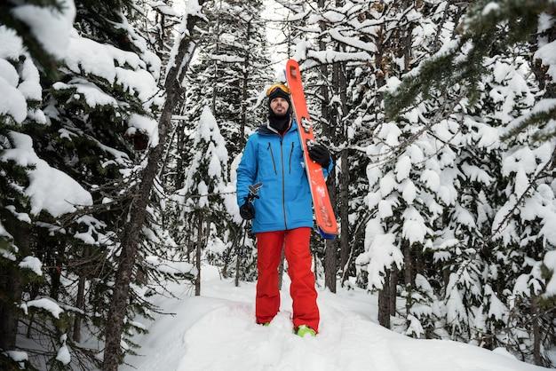 Sciatore che cammina sulle montagne innevate Foto Premium