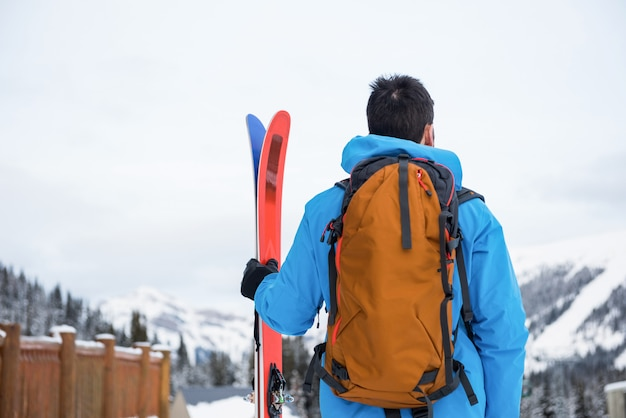 Sciatore che sta con lo sci sulle montagne innevate Foto Premium