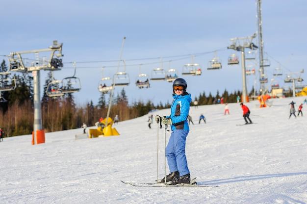 Sciatore della donna che scia in discesa alla stazione sciistica contro lo ski-lift Foto Premium