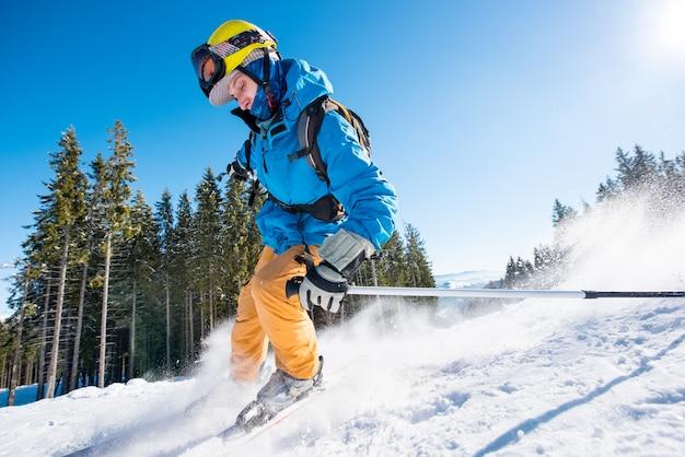 Sciatore maschio sciare sulla neve fresca in montagna in una bella giornata di sole Foto Premium