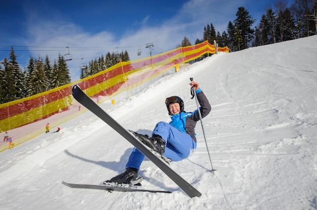 Sciatore ragazza dopo la caduta sul pendio della montagna. stazione sciistica Foto Premium