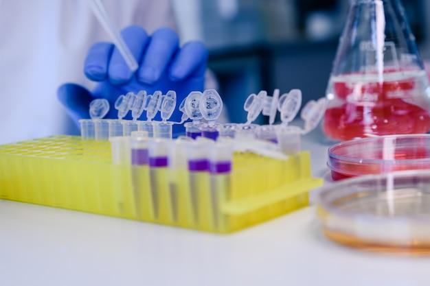 Scienziato che lavora con una pipetta e un pallone, in tubi di plastica per studi sul dna. concetto di scienza, laboratorio e studio delle malattie. Foto Premium