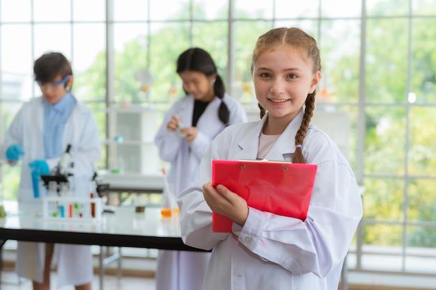 Scienziato della ragazza che sorride nella stanza del laboratorio a scuola concetto di istruzione e di formazione. Foto Premium