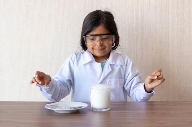 Scienziato sveglio della bambina che conduce un esperimento Foto Premium