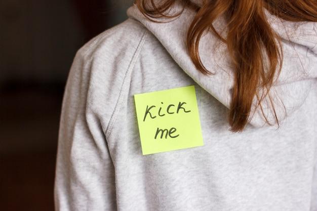 Sciocco scherzo. adesivo 'kick me' sulla schiena di una ragazza adolescente. Foto Premium