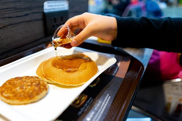 Sciroppo di versamento della mano vaga sul pancake. concetto di colazione Foto Premium