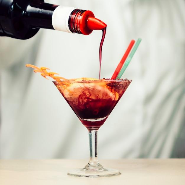 Sciroppo rosso versando nel cocktail tropicale Foto Gratuite