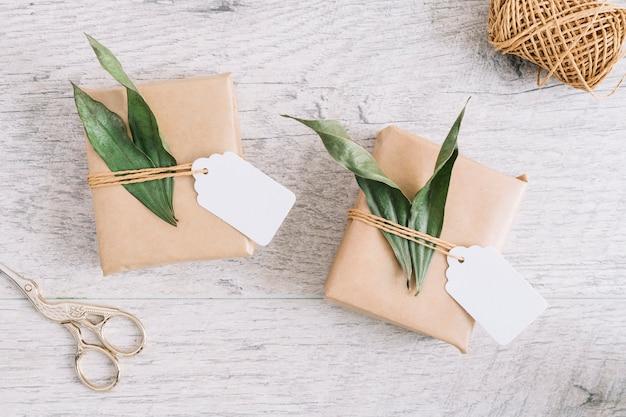 Scissor e regali avvolti con etichetta e foglie su fondo di legno Foto Gratuite