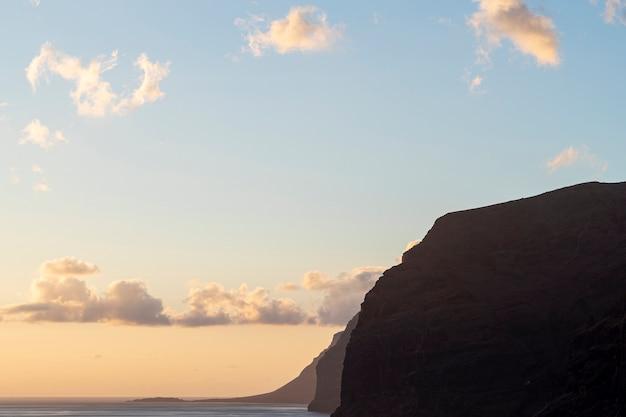 Scogliera del litorale al tramonto Foto Gratuite