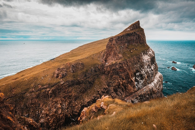 Scogliere e il villaggio sull'isola di mykines, faroe. Foto Premium