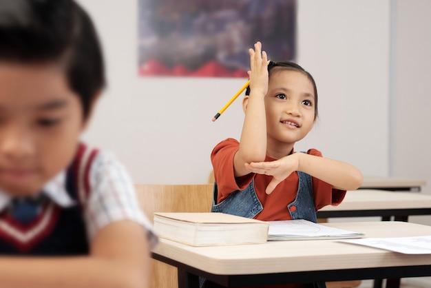 Scolara asiatica che si siede allo scrittorio in aula e che alza la sua mano per rispondere Foto Gratuite