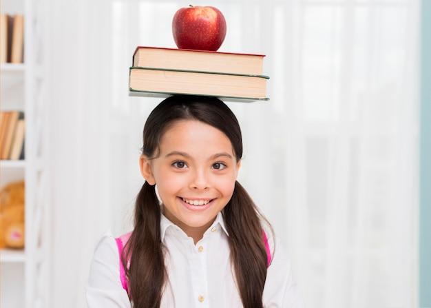 Scolara felice con i libri e la mela sulla testa Foto Gratuite