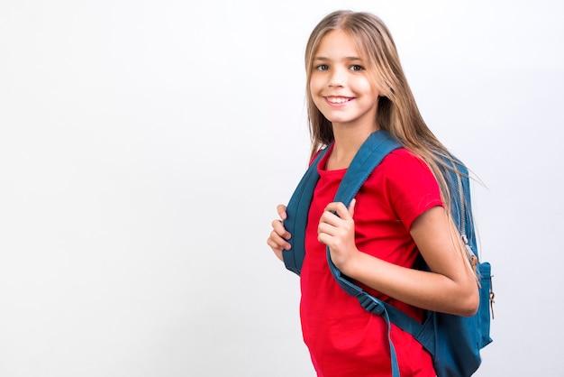Scolara sorridente che sta con lo zaino Foto Gratuite