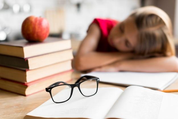 Scolara stanca che dorme allo scrittorio Foto Gratuite