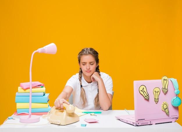 Scolara sulla scrivania con il computer portatile in stile memphis Foto Gratuite